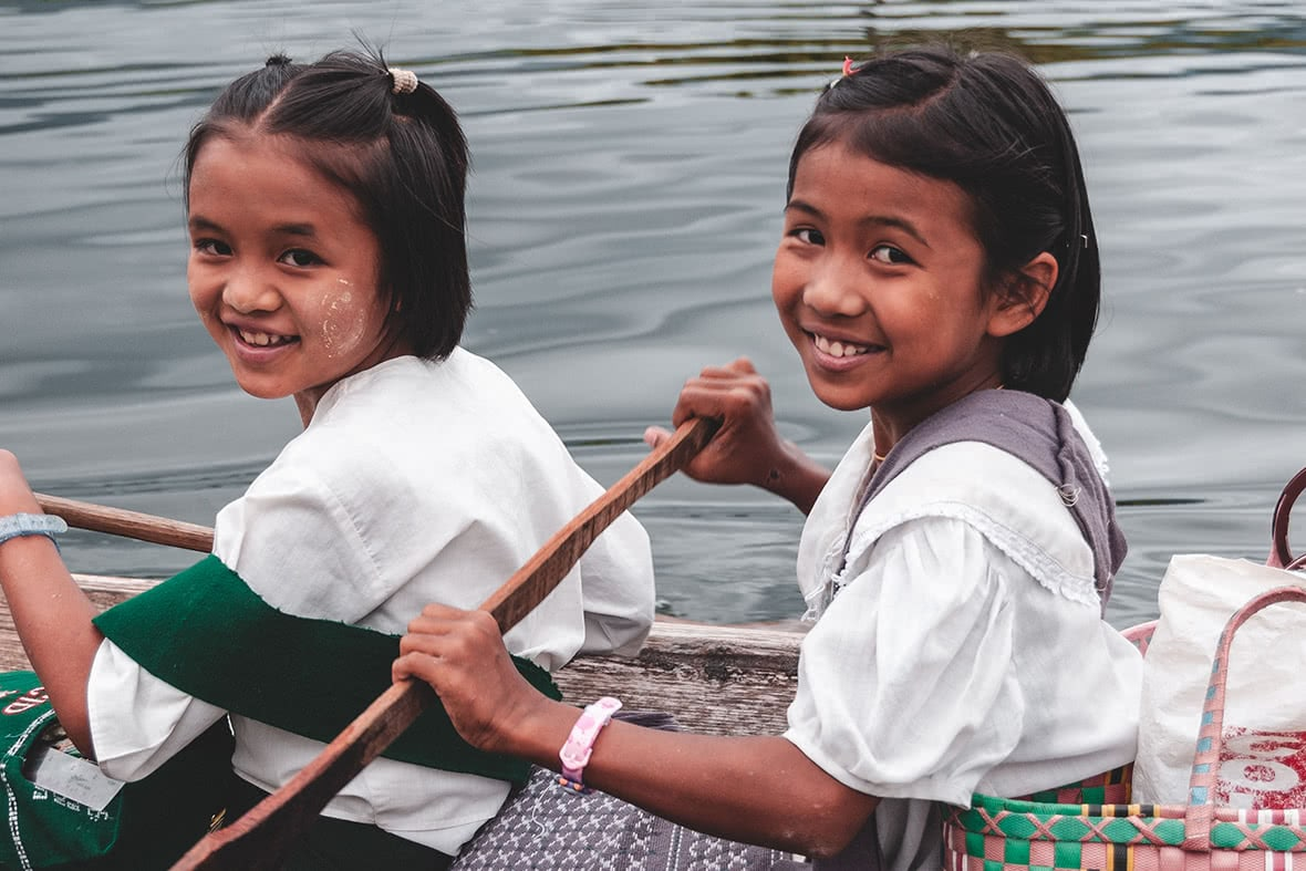 Kids go to school by boat on Inle Lake.