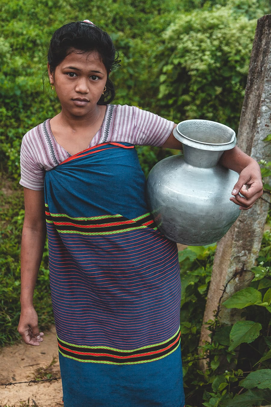 A girl fetches water from a well near her home in Bandarban, Bangladesh.