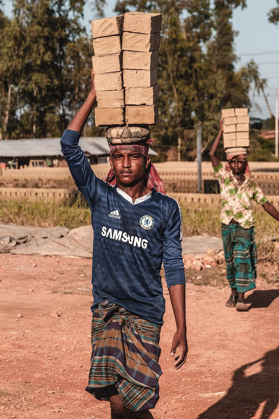 Men carrying bricks on their heads in Khulna, Bangladesh.