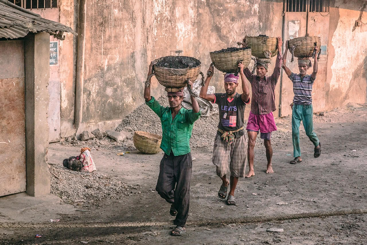 Workers carrying coal on their heads in Khulna, Bangladesh.