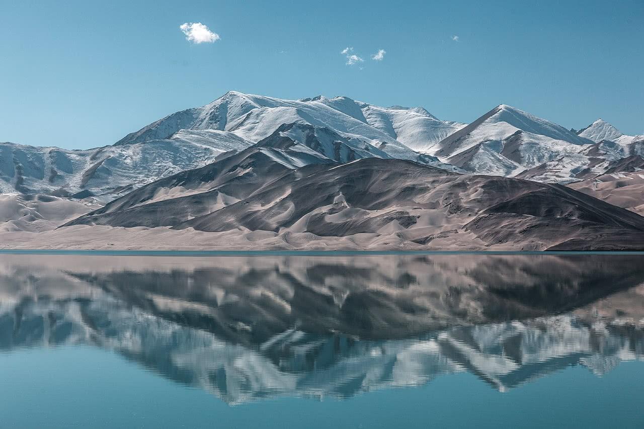Beatiful lake and snow covered mountains along the Karkoram Highway leading to Karakul Lake in western China.