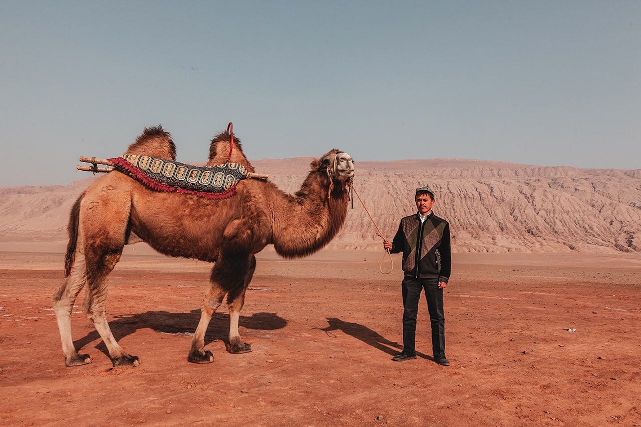 A Uyghur man and his camel, standing in front of the red sandstone cliffs of the Flaming Mountains in Turpan, western China.