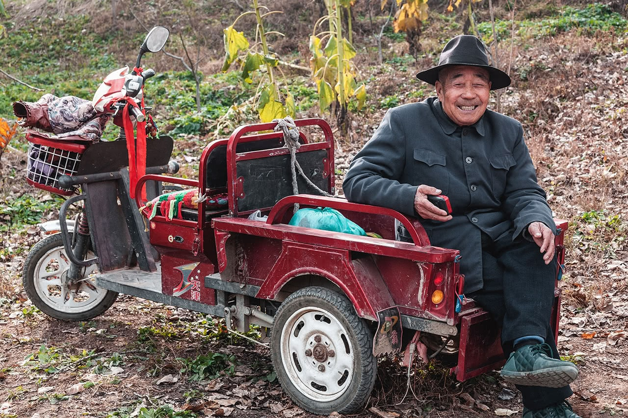 An old man sitting outside the lesser visited East Qing Tombs in China.