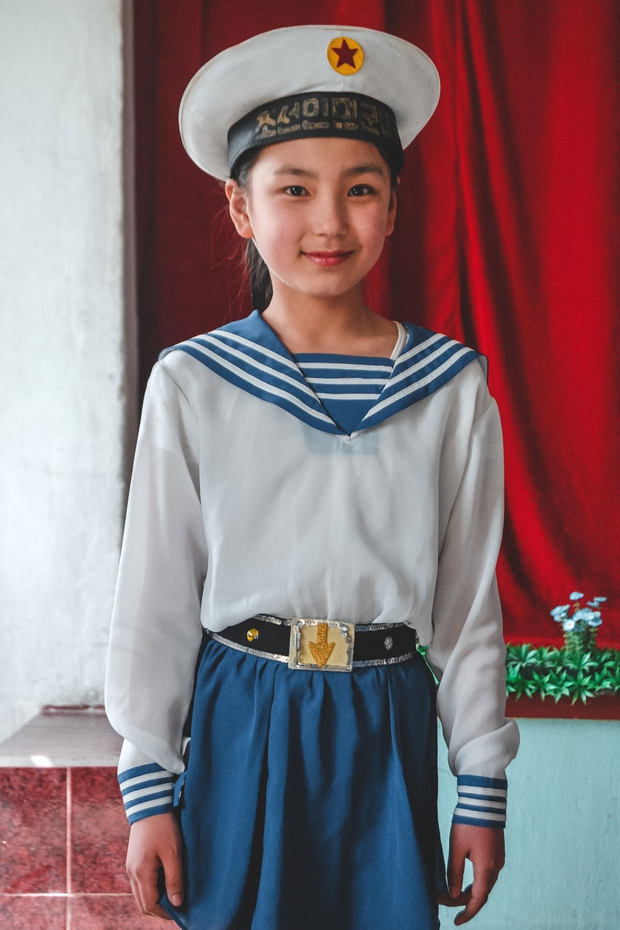 A middle school student posing for photos after performing for a group of tourists in Pyongyang.