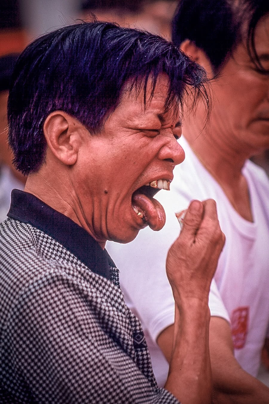 An entranced monkey god medium cuts his tongue with glass in Hong Kong.