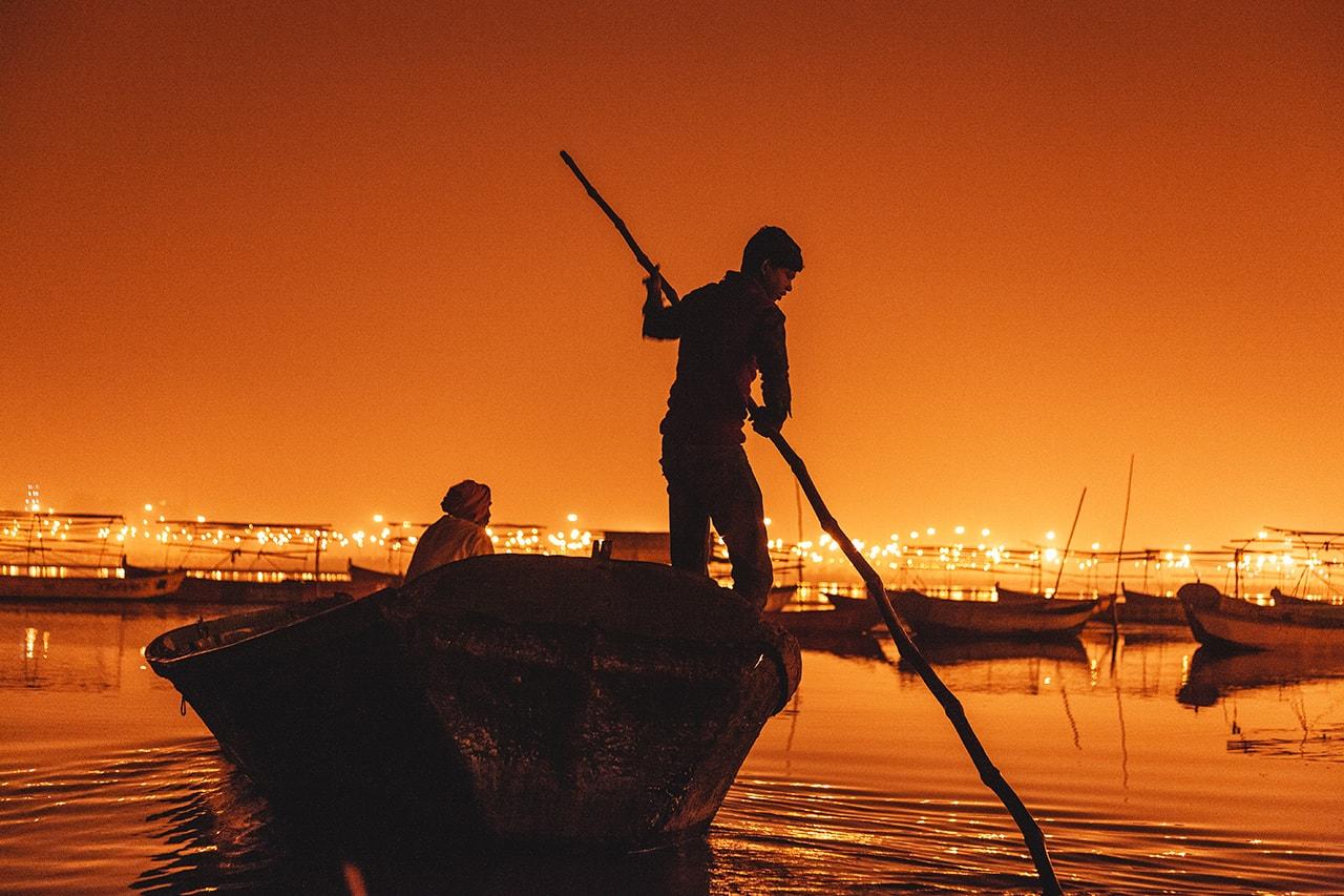 A man navigates his boat before sunrise at the Kumbh Mela in Allahabad, India.
