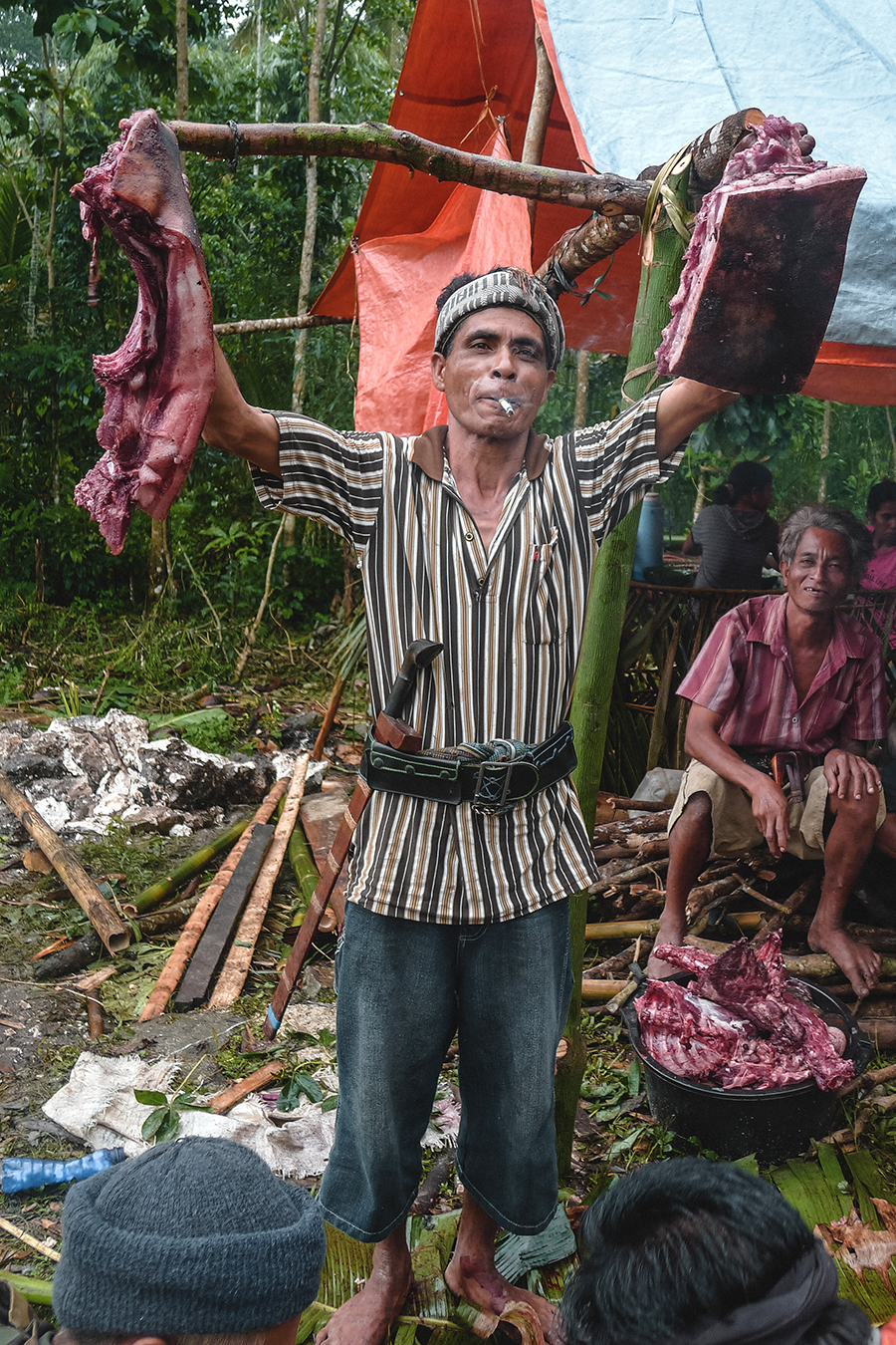 A man holding up slabs of meat from animals sacrificed during a funeral in Sumba, Indonesia.