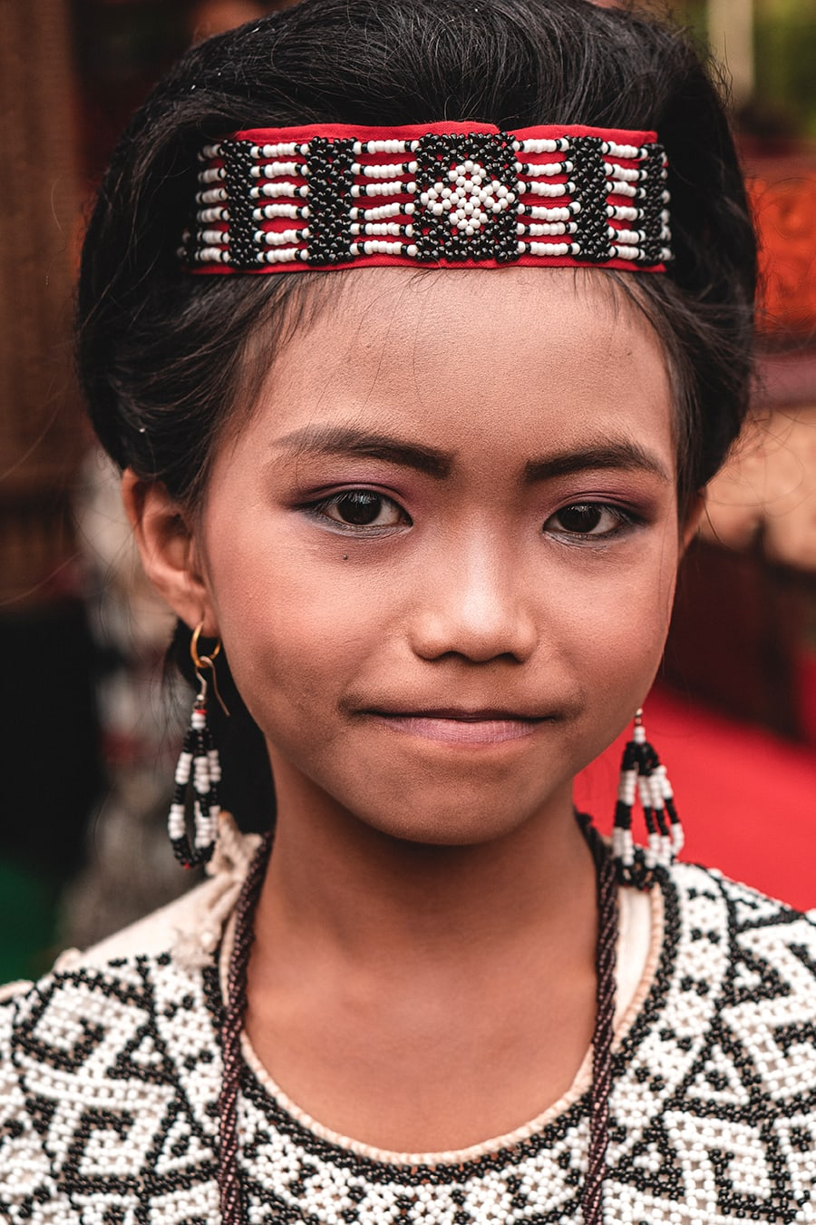 Young girl dressed in traditional attire at a Torajan funeral ceremony in Indonesia.
