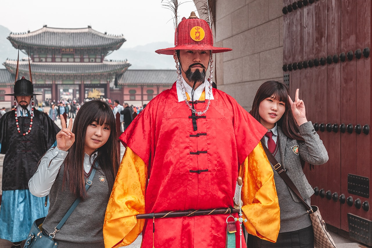 Local tourists pose with a guard at the Gyeongbokgung Palace in Seoul, Korea.