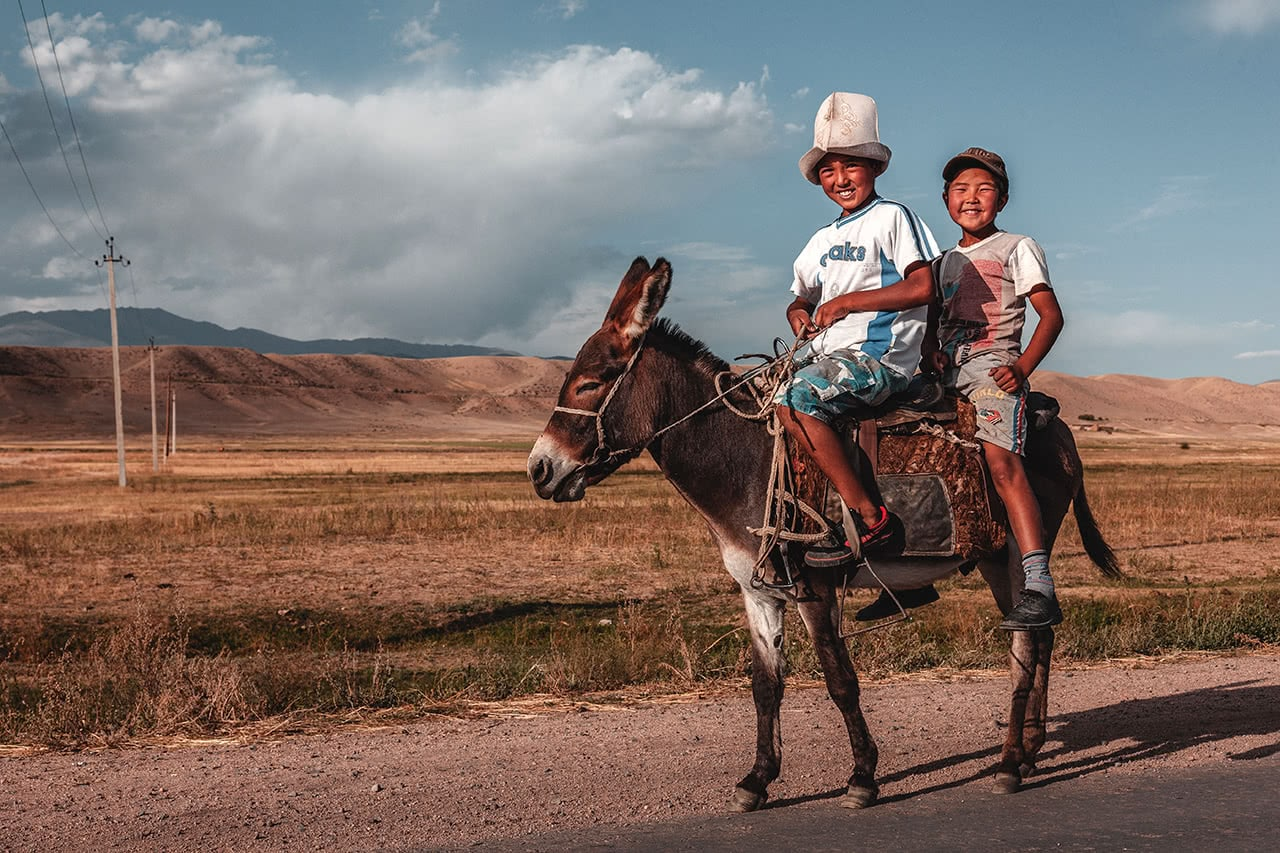 Two boys riding at donkey near the Suusamyr Valley in Kyrgyzstan.