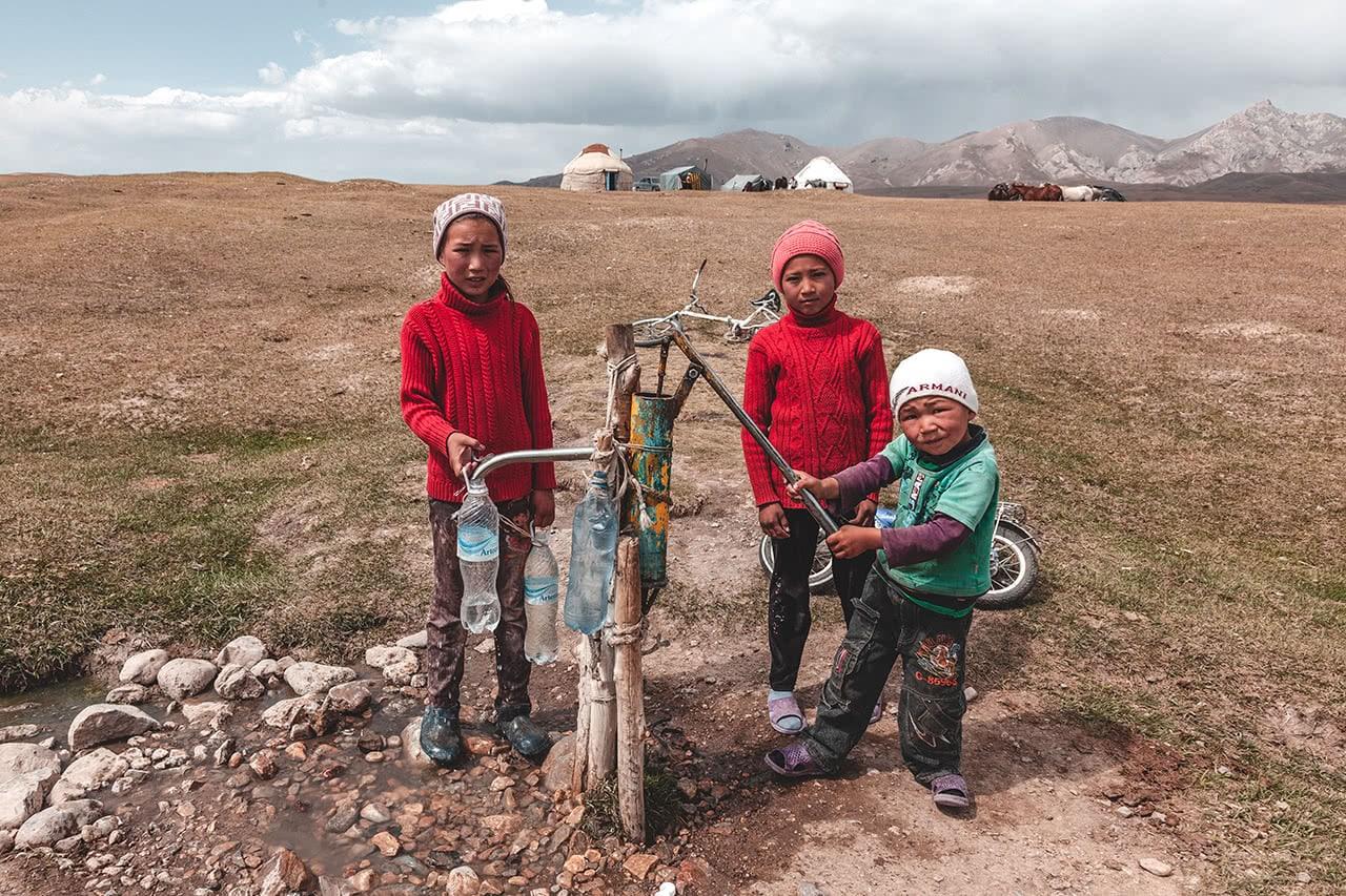 Kids pumping water at Song Kul lake, Kyrgyzstan.
