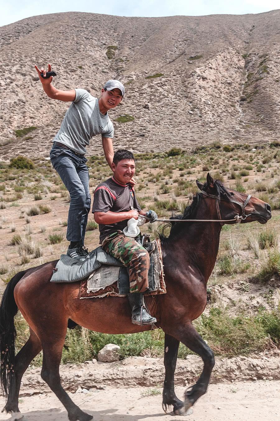 Kyrgyz men riding on horseback in the Barskoon Valley, Kyrgyzstan.