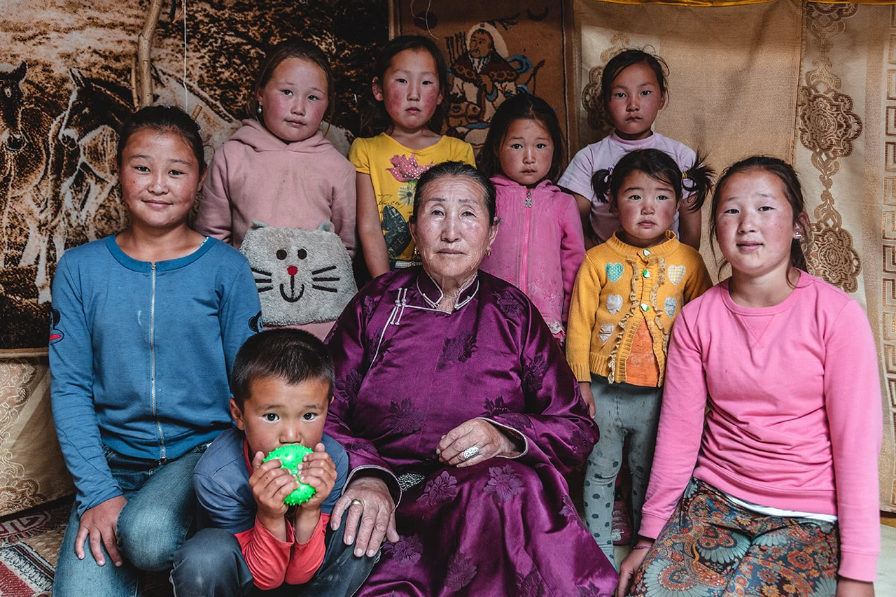 A proud grandmother with her grandchildren, in Altan Hokhii, Mongolia.