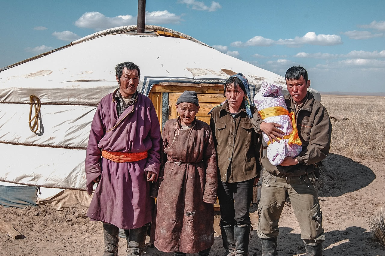 A family posing outside their ger in the Gobi desert, Mongolia.