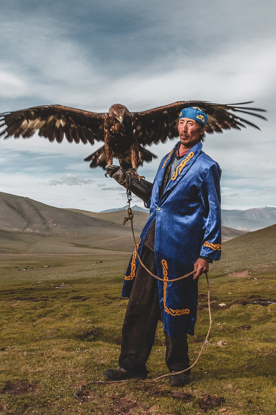 A Kazak eagle hunter poses with Tsambagarav Uul in the background.