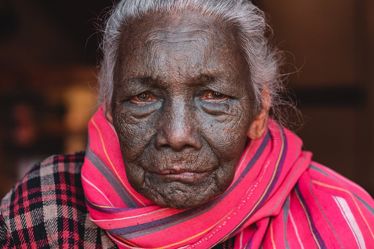 An 86 year old U-Pu Chin woman, whose entire face was tattooed in black ink.