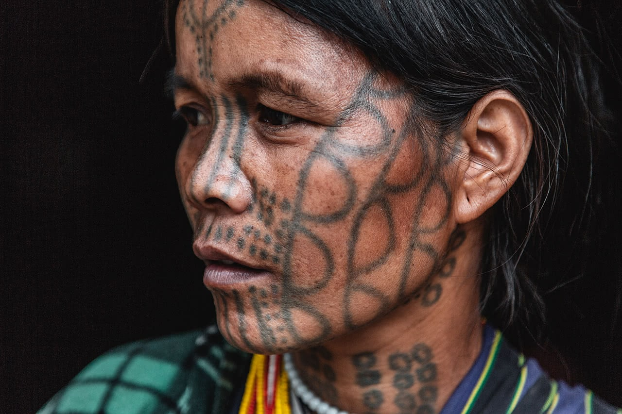 """Munn Chin woman with distinctive """"b"""" shape tattoos on her face."""