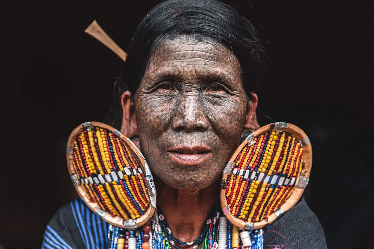 A woman from the M'kuum tribe, with tattooed face and unusually large earrings.
