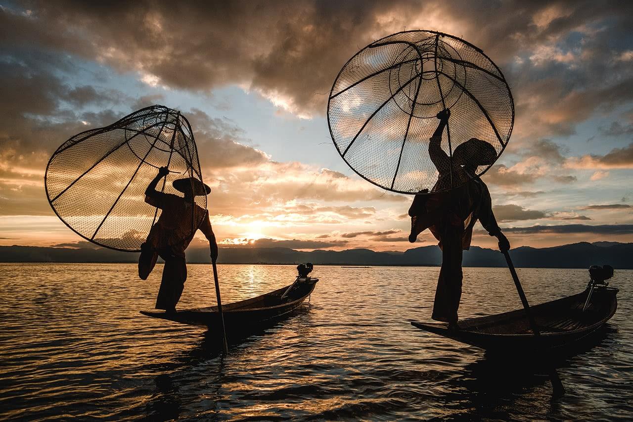Leg-rowing fisherman at Inle Lake at sunset.