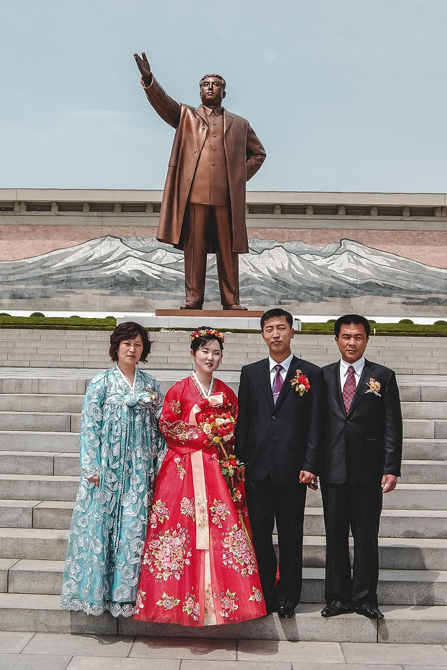 A newly married couple poses for photos in front of a statue of the Dear Leader, Kim Il-Sung in Pyongyang.