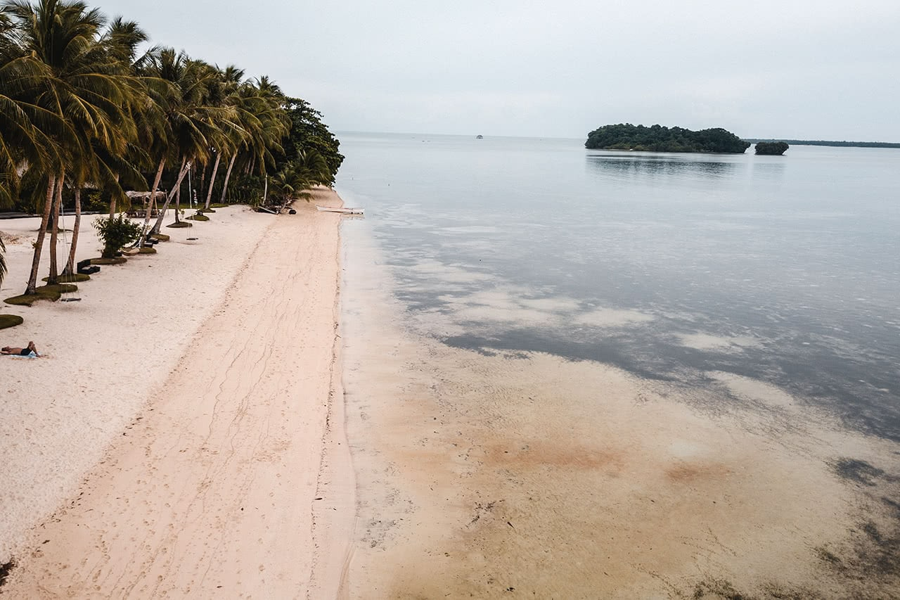 Drone view of the beach in front of Nay Palad Hideaway, in Siargao, Philippines.