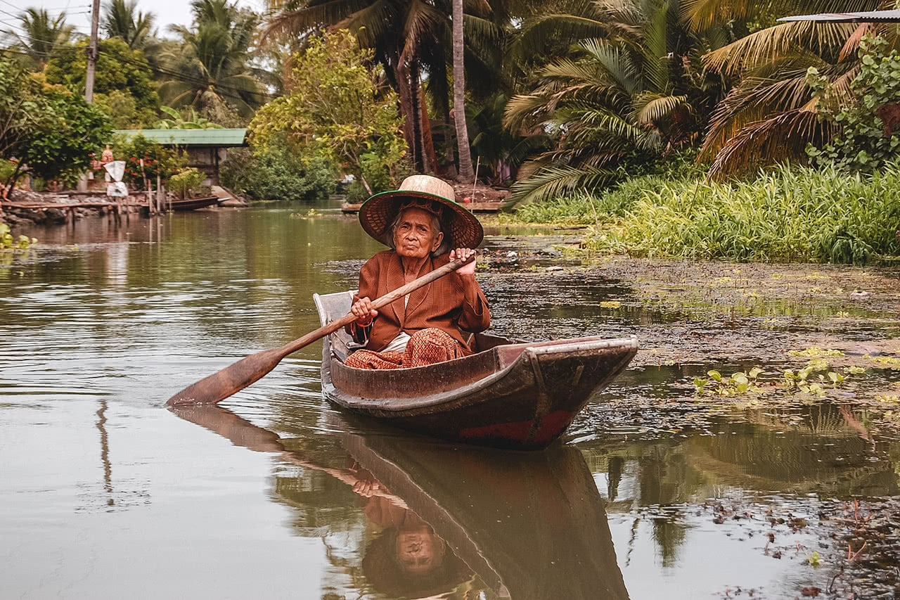A woman paddles a boat through Taka Market in Thailand.