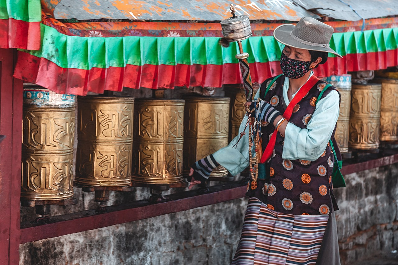 A worshipper spinning prayer wheels at the base of Potala Palace in Lhasa.