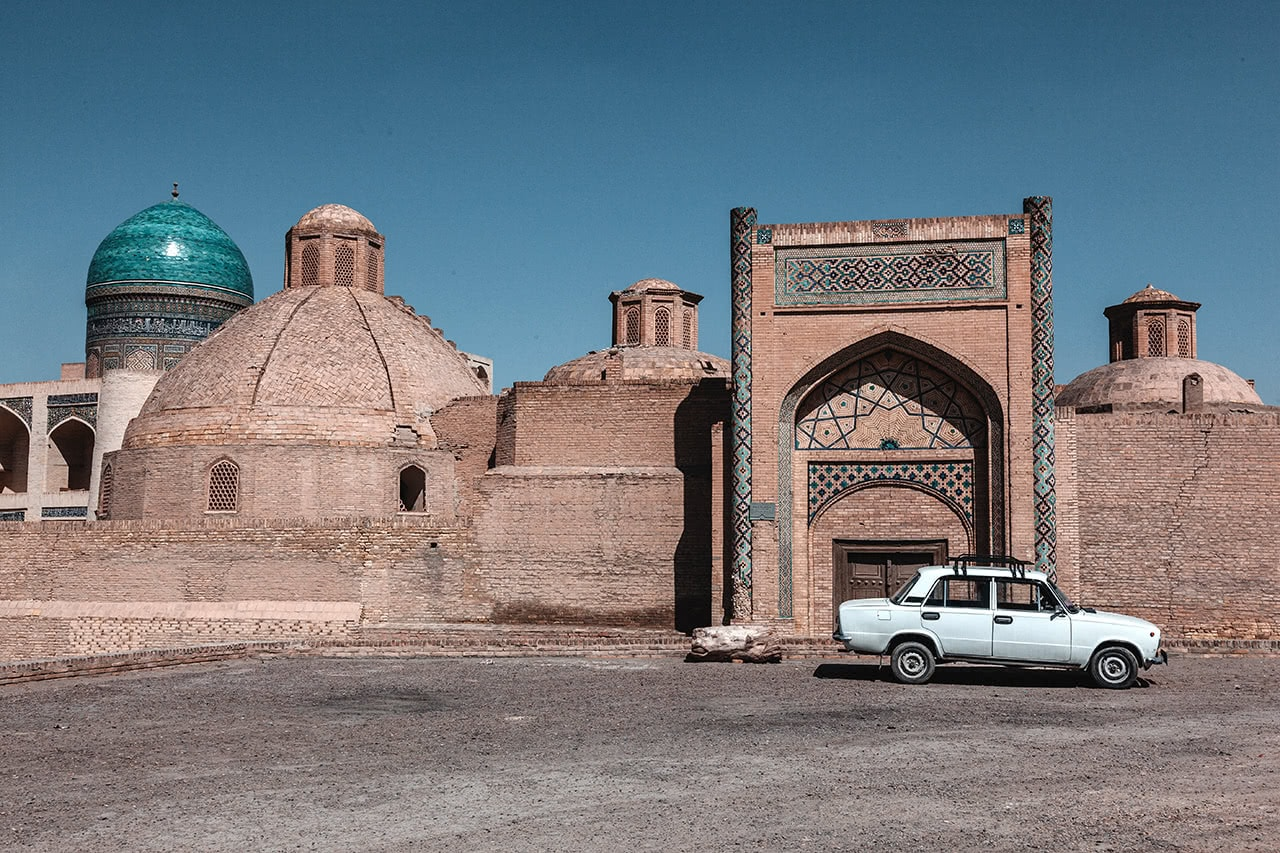 A Russia Lada parked in front fo the ancient structures of Bukhara.