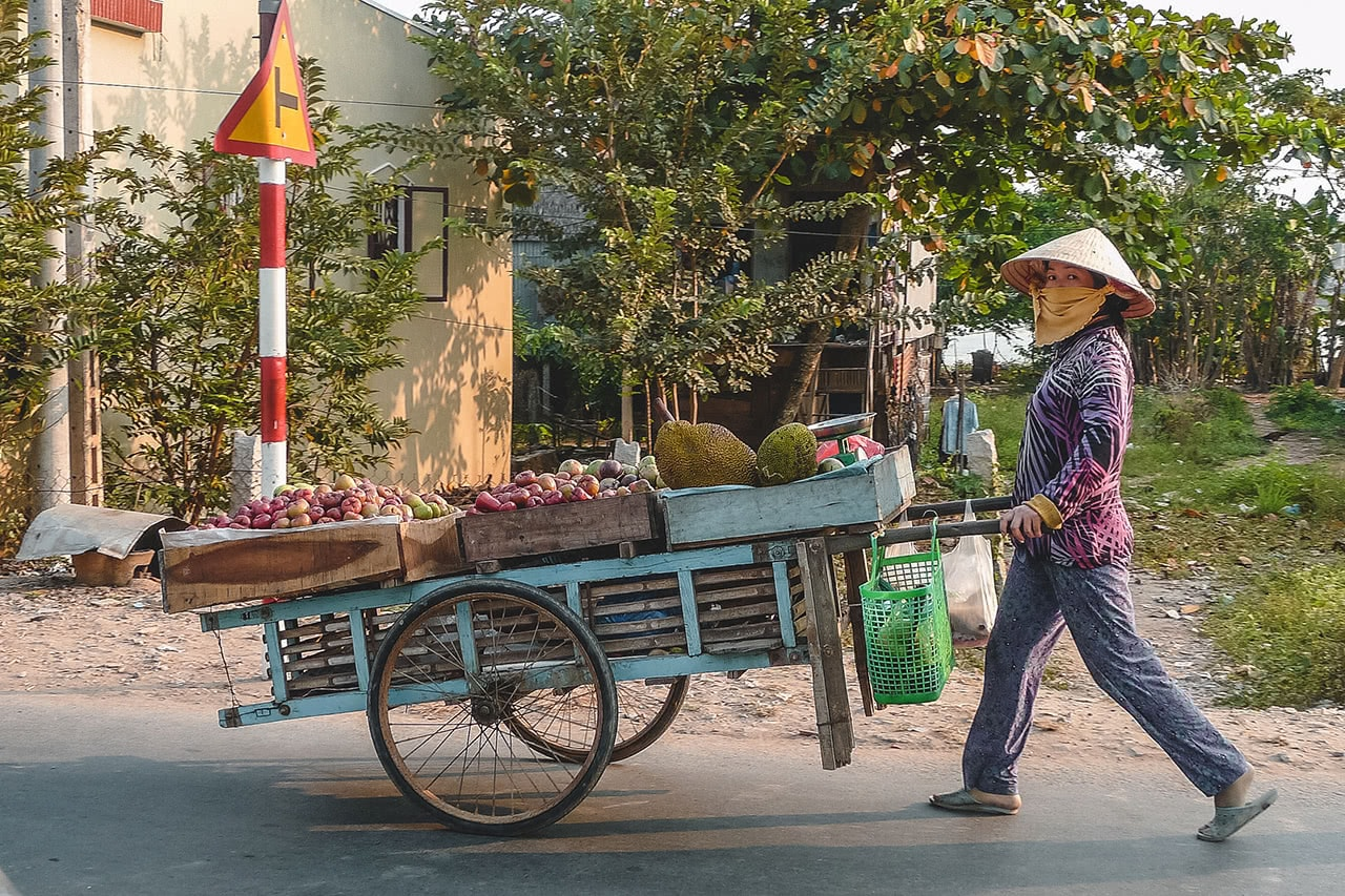 Food vendor looking cautiously at my camera in Chau Doc