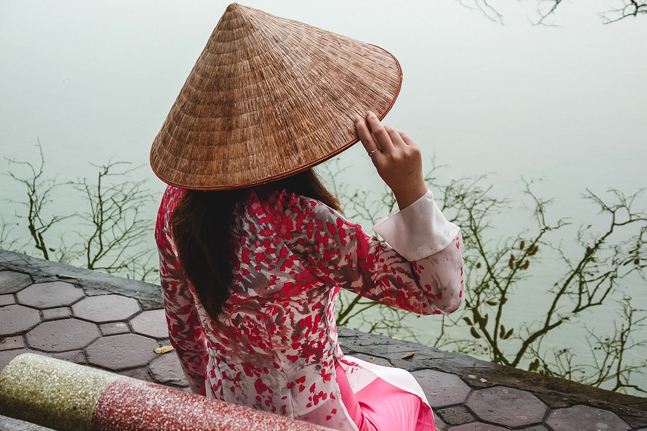 A Vietnamese woman wearing a traditional Ao Dai at Hanoi's Hoan Kiem Lake